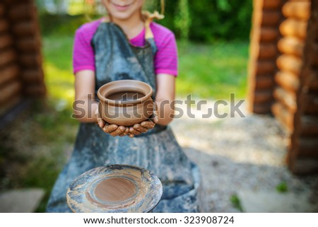 Little smiling girl produced on potters wheel pot. - stock photo