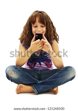 Little smiling girl reading sms on your cell phone. Isolated on white background