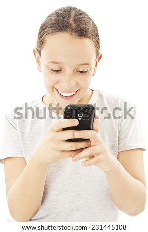 Little smiling girl reading sms on your cell phone. Isolated on white background  - stock photo