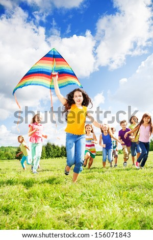 Little smiling girl running with kite and large group of happy friends together in the park
