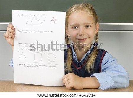 Little, smiling girl sitting at dest in front of blackboard with test in hands. Smiling and looking at camera. Front view - stock photo