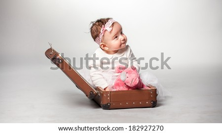 Little smiling girl sitting in suitcase with pink teddy bear - stock photo