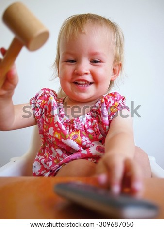 Little smiling girl trying to break the mobile telephone with wooden hammer. - stock photo