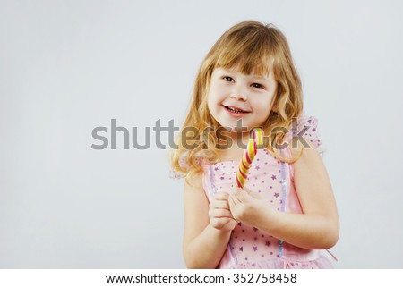 Little smiling girl, with curly blond hair, wearing on pink dress, holding colorful candy in her hands, on white background, in studio, waist up