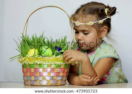 Little smiling girl with Easter basket with eggs decorated with the grass after egg hunt, happy family holiday