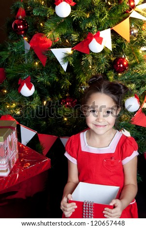 Little smiling girl with red gifts at Christmas night - stock photo
