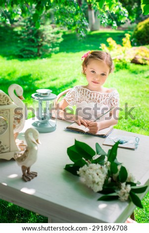 Little smiling girl  writing on notebook outdoor in the park. Vintage style. Facial expression. - stock photo