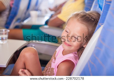 Little smiling happy girl in the aircraft - stock photo