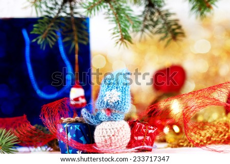 Little snowman figurine and gift boxes on the christmas decorations background
