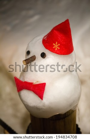 little snowman on wooden pole
