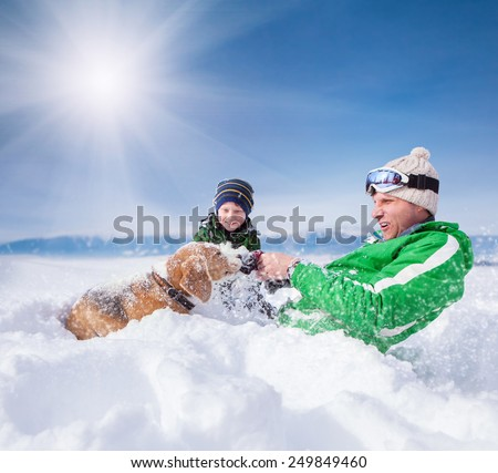 Little son and father playing with beagle in deep snow - stock photo