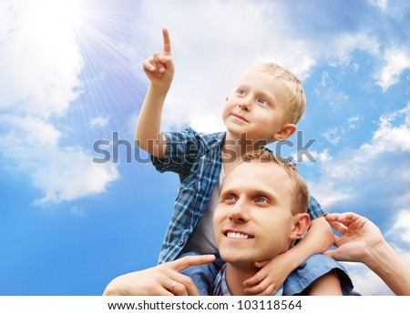 Little son at father's shoulders on blue sky background - stock photo