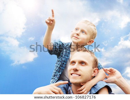 Little son at father's shoulders on blue sky background
