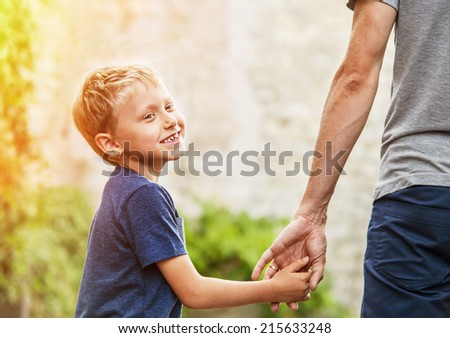 Little son hold his father for hand - stock photo