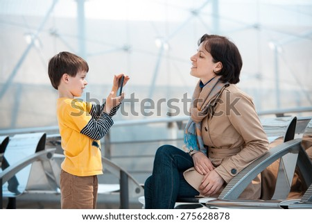Little son photographing his mother at airport, going on holiday - stock photo