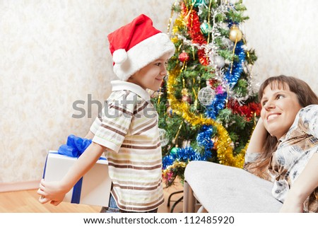 Little son wearing Santa Claus hat giving new year present or christmas holiday gift box to smiling mother - stock photo