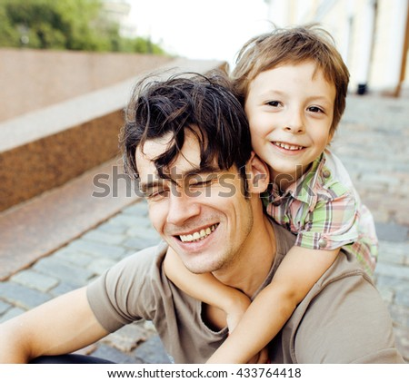 little son with father in city hagging and smiling, casual look outside playing, happy real family, lifestyle people concept - stock photo