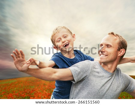 Little son with father on the poppies field - stock photo
