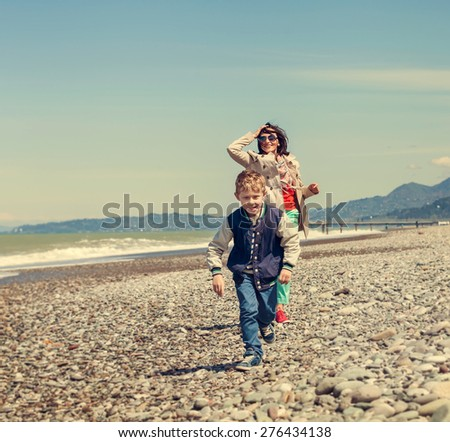 Little son with mother runs together at the sea coast - stock photo