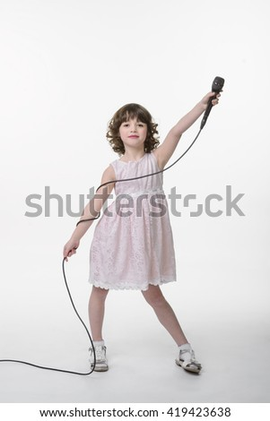 Little star of the scene with rised hand in which she holds the microphone. The other hand is braided with the cable. Young lady smiles and looks right in the camera. - stock photo