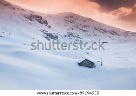 little stone cabin in winter sunset, plenty of snow - stock photo