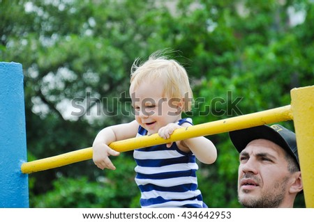 Little strong baby toddler with his father playing sports outdoor. Children during his workout.