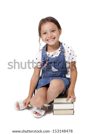 little student girl sitting on stack of books isolated on a white background - stock photo
