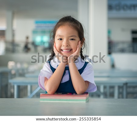 little student girl with a book at school - stock photo