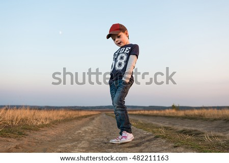 little stylish boy on countryside road