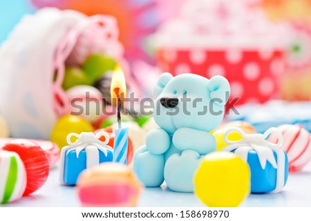 little sugar teddy with a candle and candies - stock photo