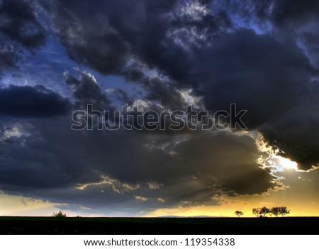 Little sun between gray clouds - stock photo