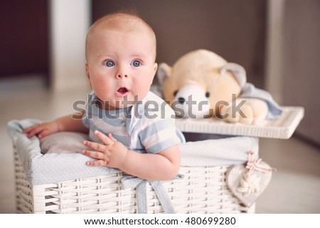 Little surprised baby in white wicker basket