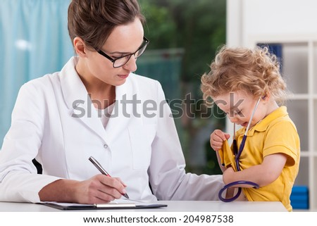 Little sweet boy playing doctor with stethoscope during medical visit