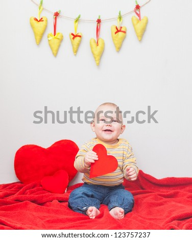 little sweet boy playing with heart on a red blanket