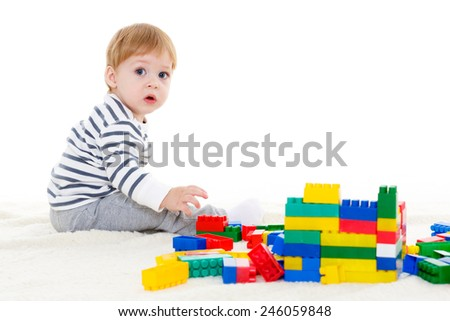 Little sweet boy plays with children blocks set on a white background. Early development and learning toys. - stock photo