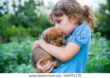 Little sweet curly girl with a red puppy on hands  - stock photo