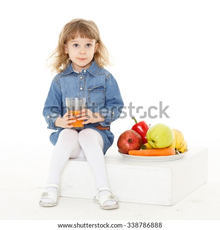 Little sweet girl drinks fresh juice on a white background. Healthy food. 3 year old. - stock photo