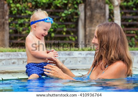 Little swimming child in underwater goggles sit on poolside, has fun - baby play with   smiling woman in pool. Family lifestyle and summer children water sports outdoor activity and lesson with parent - stock photo