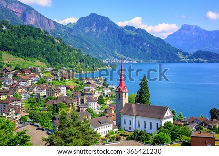Little swiss town with gothic church on Lake Lucerne and Alps mountain, Switzerland - stock photo