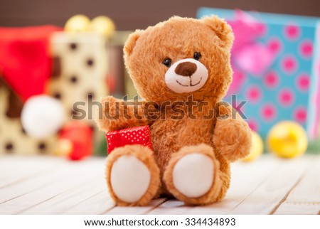 Little teddy bear with gift on christmas background