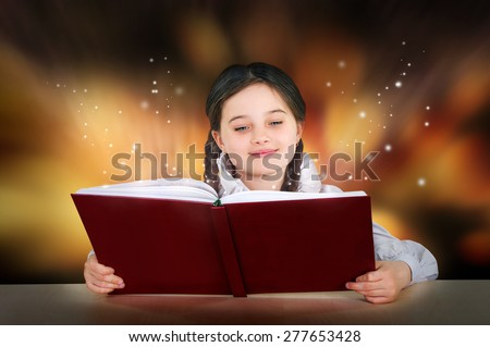 Little teen girl reads a magical fairy tutorial book smiling - stock photo