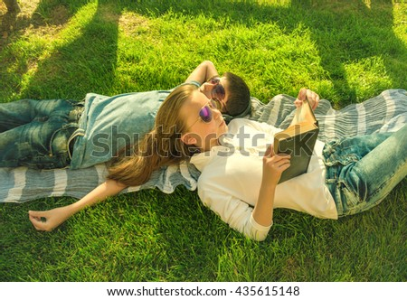 Little teenage boy and girl are lying on grass, girl reads book and boy wears earphones  - stock photo