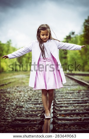 little thai girl balancing on a railroad track, vintage effect added