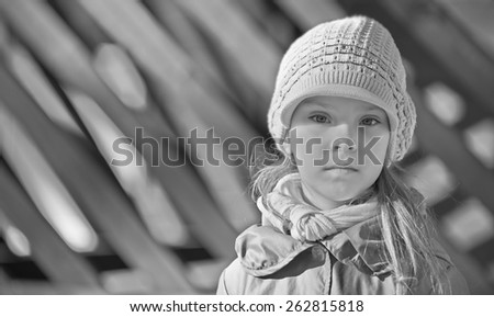 Little thoughtful beautiful girl in a cap and a jacket around the house. - stock photo