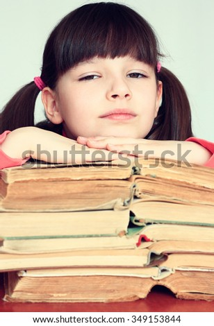 Little thoughtful girl sitting on a pile of books. - stock photo