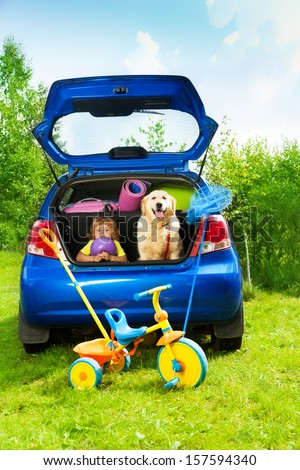 Little three years old boy sitting in the car trunk with a dog waiting for parents to put bags and tricycle for the trip in the car - stock photo