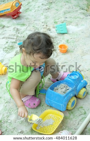 Little toddler, adorable blonde toddler girl, enjoying hot sunny summer day at the playground sitting inside big sandbox and playing with sand, shovel and toy bucket. Terrible twos.