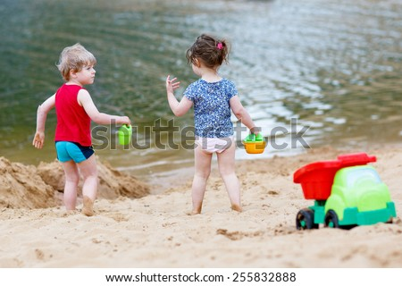 Little toddler boy and girl playing together with sand toys near city lake on hot summer day. Active outdoors leisure with kids in summer, on sunny ay. - stock photo