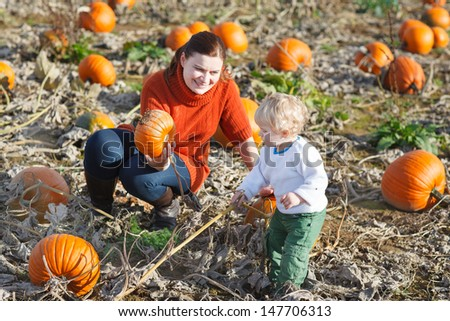 Little toddler boy and his mother in a field of pumpkins