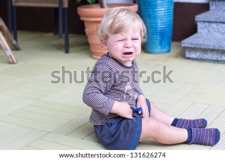 Little toddler boy crying outdoors in summer